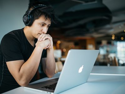 Young man with headphones looking at a laptop computer