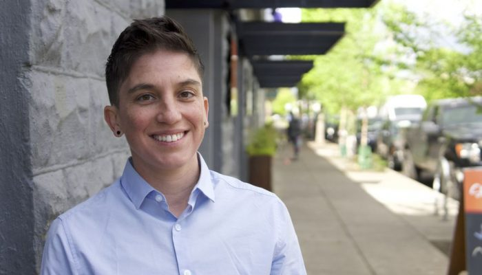 Young non-binary person with short hair in a blue shirt