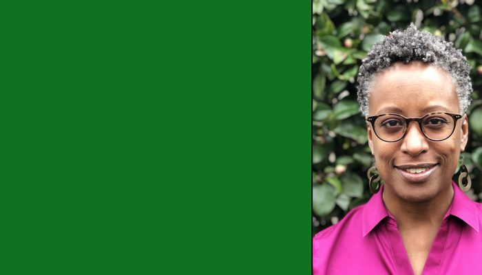 Black woman with gray hair, wearing glasses and bright pink shirt smiles at the camera
